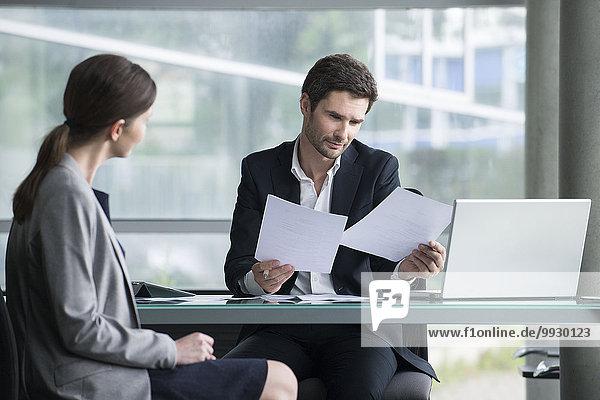 Geschäftsmann bei der Prüfung von Dokumenten mit dem Kunden