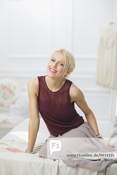 sitzend Frau lächeln Bett