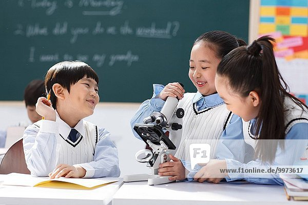 Elementary school students in the classroom with a microscope