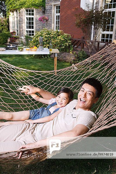Father and daughter lying in a hammock in the garden