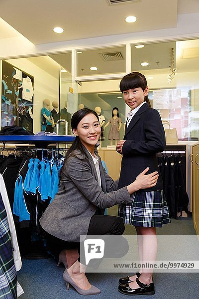 Female teachers is to help primary school girls trying on school uniforms