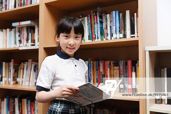 Primary school girl read a book in the reading room