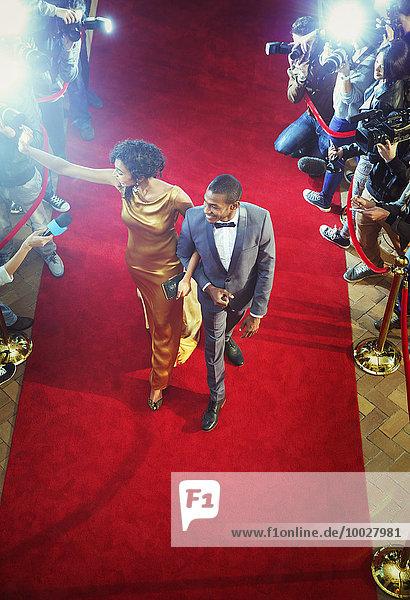Berühmtheitspaar kommt zur Veranstaltung und winkt und geht über den roten Teppich