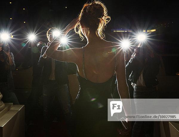 Silhouette einer Berühmtheit  die von Paparazzi fotografiert wird.