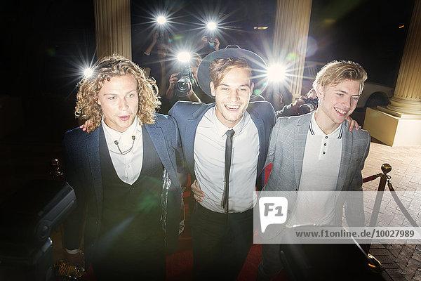 Lächelnde Berühmtheiten gehen in einer Reihe auf dem Roten Teppich