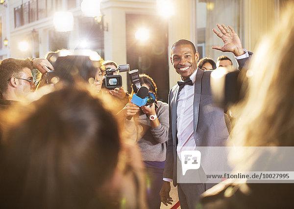 Prominente winken für Paparazzi mit Kameras bei der Veranstaltung