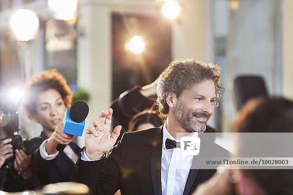 Berühmtheit winkt Paparazzi bei der Veranstaltung zu