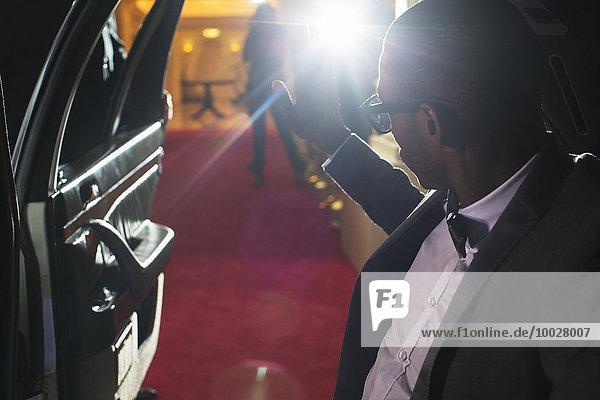 Berühmtheit in der Limousine beim Eintreffen auf dem roten Teppich und beim Fotografieren von Paparazzi
