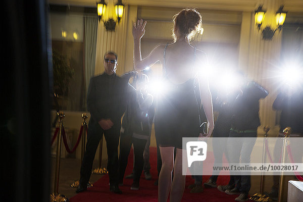 Silhouette einer Berühmtheit in schwarzem Kleid  die bei der Veranstaltung ankommt und den Paparazzi-Fotografen winkt