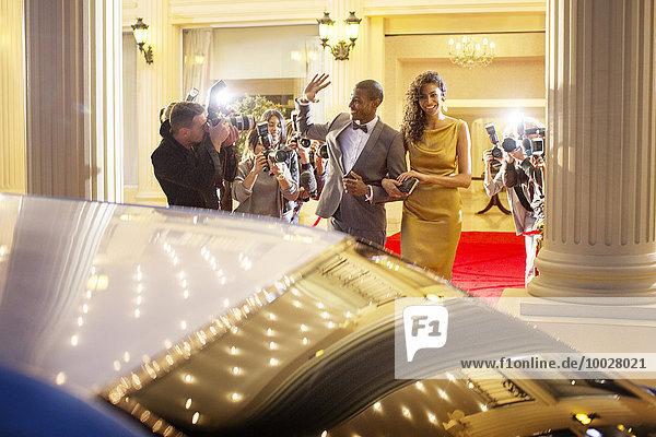 Prominentenpaar winkt Paparazzi-Fotografen zu und verlässt die Veranstaltung