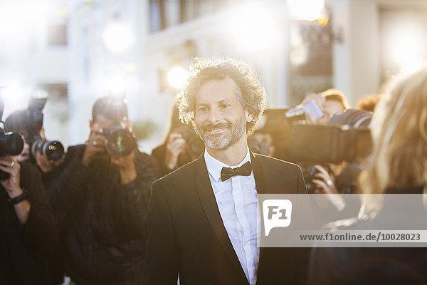 Lächelnde Berühmtheit  fotografiert von Paparazzi bei der Veranstaltung