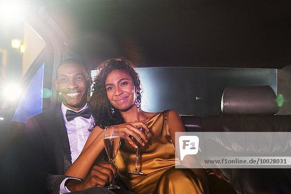 Lächelndes Promi-Paar trinkt Champagner in der Limousine außerhalb der Veranstaltung
