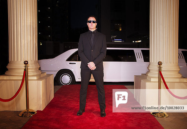 Seriöser Bodyguard mit Sonnenbrille zum Schutz des roten Teppichs bei der Veranstaltung