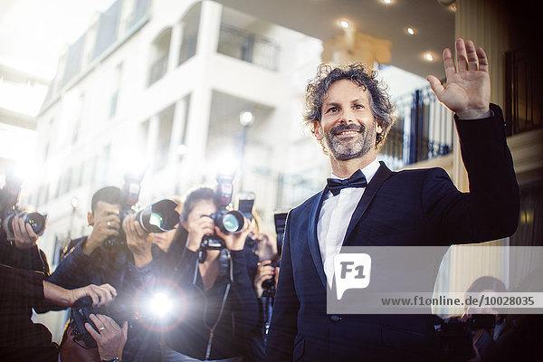 Berühmtheit winkt Paparazzi-Fotografen bei der Veranstaltung zu