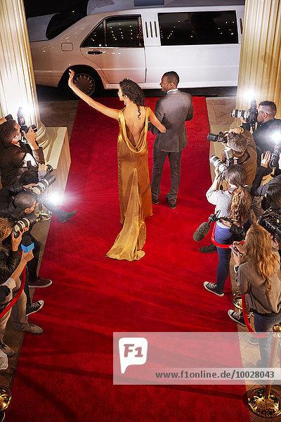 Promi-Paar winkt Paparazzi-Fotografen zu und verlässt den roten Teppich.