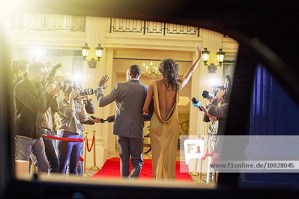 Promi-Paar kommt an und winkt den Paparazzi-Fotografen auf dem roten Teppich zu