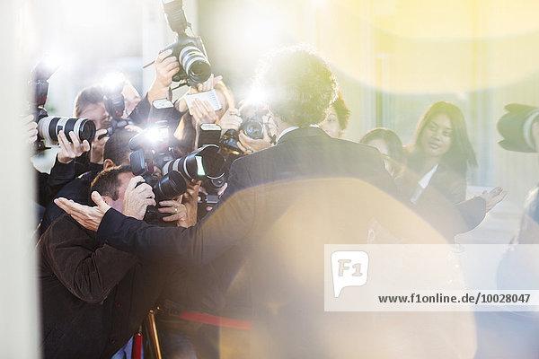 Berühmtheit  die von Paparazzi bei der Veranstaltung fotografiert wird.