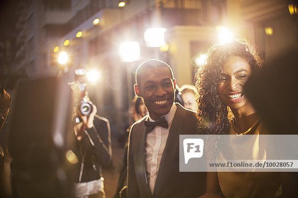 Lächelndes Promi-Paar wird von Paparazzi bei der Veranstaltung fotografiert
