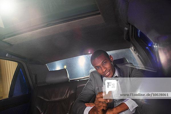 Porträt eines selbstbewussten Prominenten  der einen Cocktail in der Limousine trinkt.