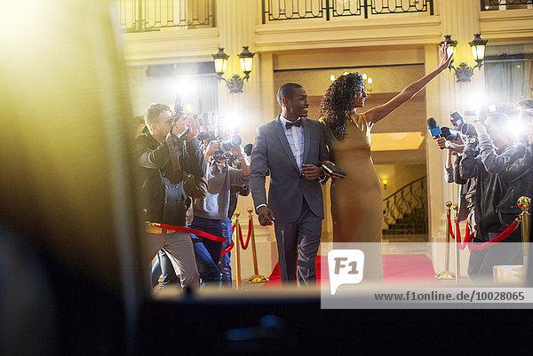 Promi-Paar verlässt den roten Teppich und winkt den Paparazzi-Fotografen.