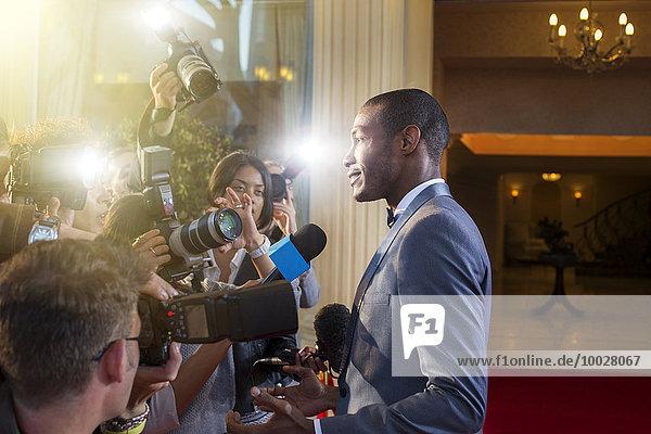 Berühmtheit wird von Paparazzi beim Red Carpet Event interviewt und fotografiert.