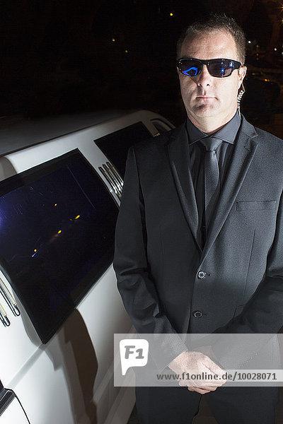 Porträt eines seriösen Bodyguards mit Sonnenbrille vor der Limousine bei der Veranstaltung
