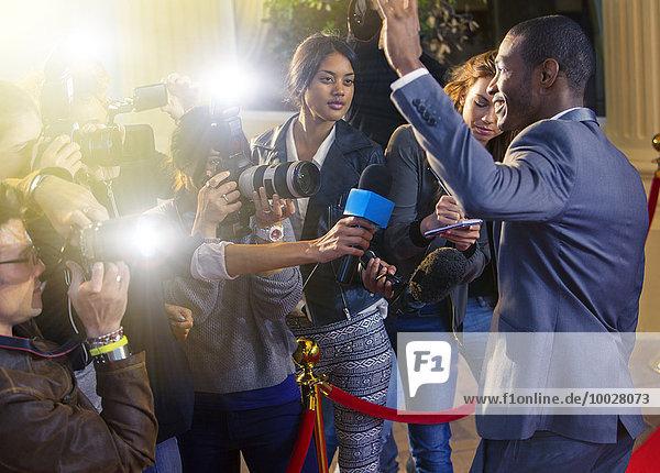 Prominente winken bei Paparazzi-Fotografen auf dem Roten Teppich