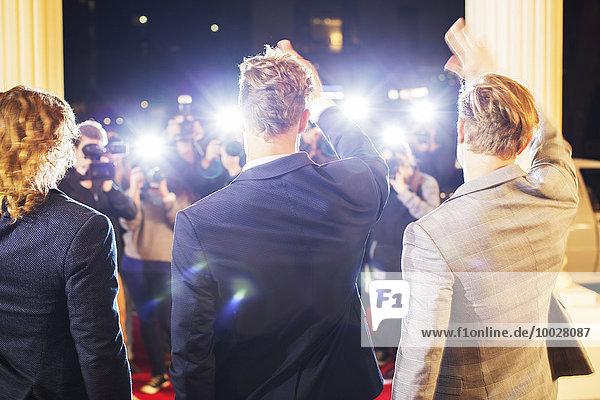 Prominente winken und werden von Paparazzi-Fotografen auf dem roten Teppich fotografiert.