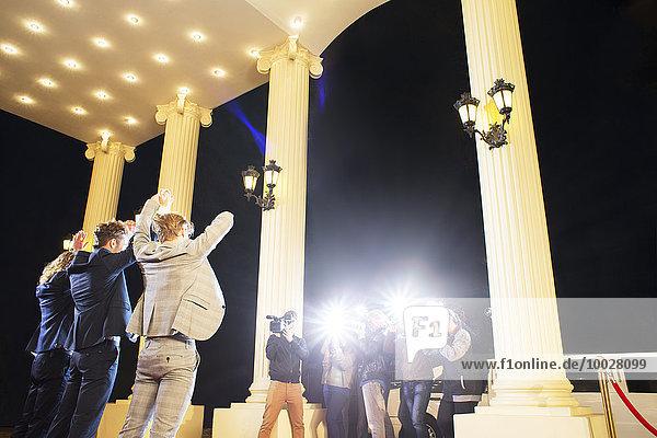 Prominente posieren mit erhobenen Armen für Paparazzi-Fotografen bei der Veranstaltung