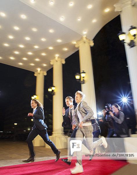 Enthusiastische Prominente kommen und laufen von Paparazzi-Fotografen auf dem Roten Teppich
