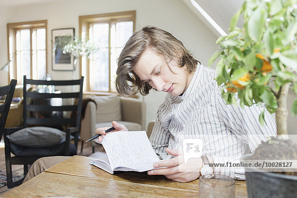 Young man reading notes from book at table in restaurant