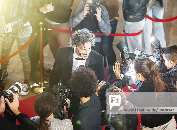 Celebrity being interviewed and photographed by paparazzi photographers at red carpet event