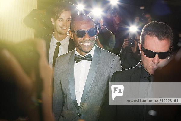 Lächelnde Berühmtheit mit Sonnenbrille  fotografiert von Paparazzi-Fotografen bei der Veranstaltung.