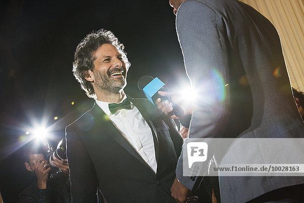 Lächelnde Berühmtheit wird von Paparazzi auf der Veranstaltung interviewt und fotografiert.