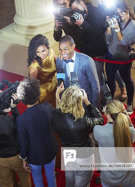 Prominentenpaar wird von Paparazzi beim Red Carpet Event interviewt und fotografiert.