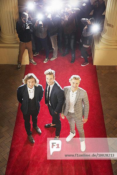Porträt von lächelnden Prominenten auf rotem Teppich