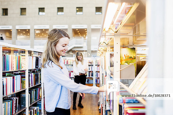 Side view of woman choosing book in library