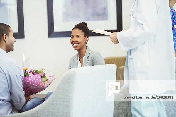 Arztbesprechung mit lächelndem Paar im Wartezimmer des Krankenhauses