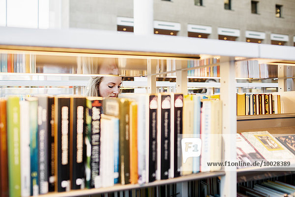Young female university student seen through books and shelf in library