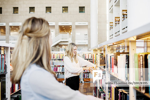 Happy female student choosing book with friend in foreground at library