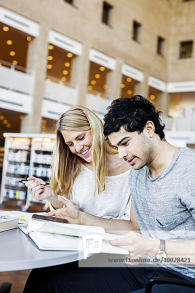 Happy young friends with mobile phone reading notes in library