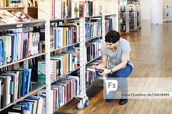 Young man holding book while kneeling in library