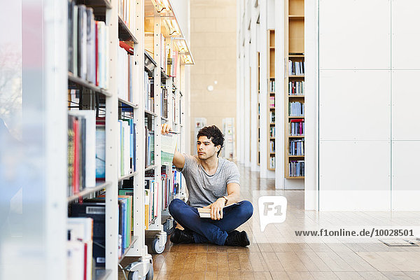 Young man sitting choosing book while crossed legged in library