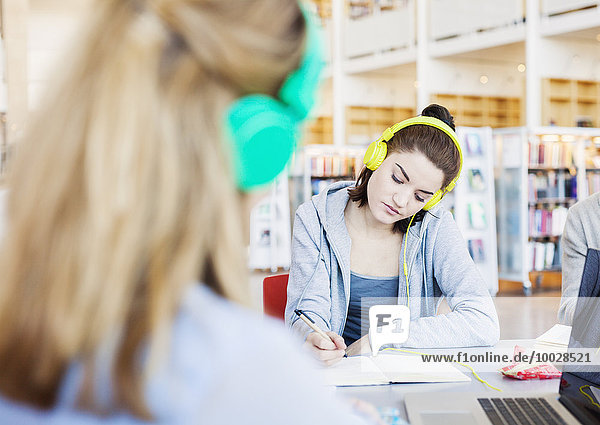 Young woman writing notes while listening to lecture through headphones at table in library