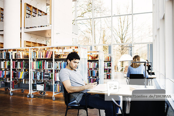 Young man holding mobile phone at table in library