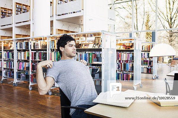 Young man stretching while sitting at table in library