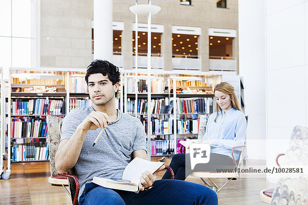 Portrait of young man holding book in library