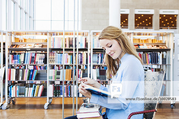 Side view of young woman reading book in library