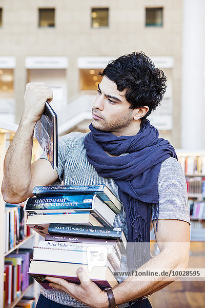 Young man choosing books in library