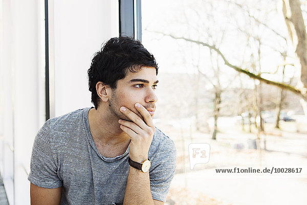 Thoughtful young man with hand on chin looking through window in library